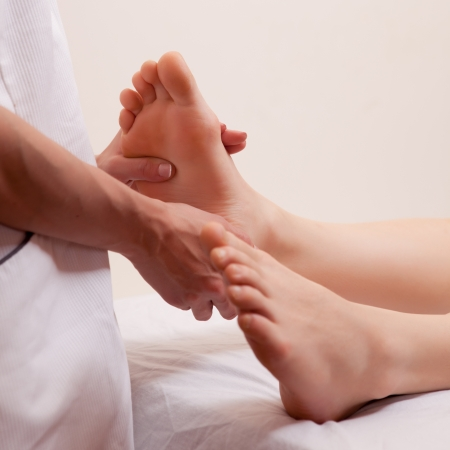 A close-up detail of a masseur giving a foot massage photo