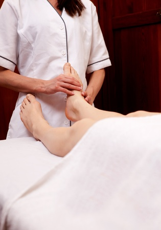 A masseur giving a professional foot massage in an old style spa photo