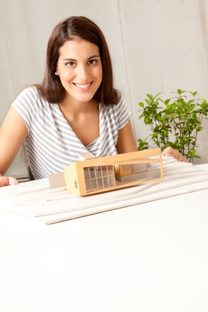 functionalism: A young female architect smiling at the camera with a house model