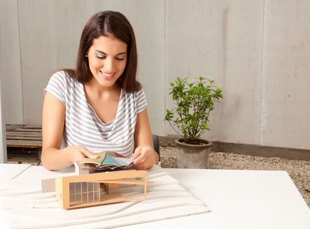 functionalism: A young female architect looking at color swatches with a model house