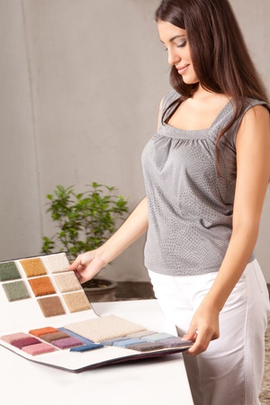 A female interior designer looking at carpet swatches in a catalogue photo
