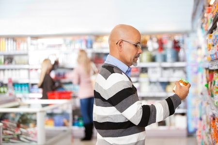 superstore: Mature man shopping in the supermarket with people in the background