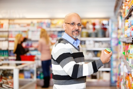 Portrait of a mature man shopping in the supermarket with people in the background Stock Photo - 9470774
