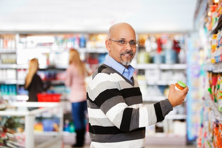 Smiling mature man shopping in the supermarket with people in the background photo