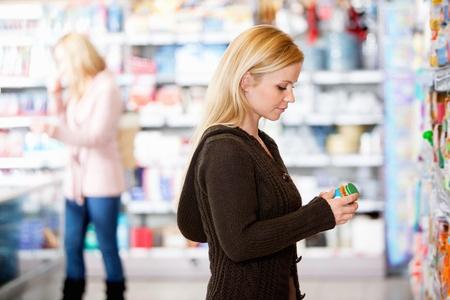 gamme de produit: Jeune femme shopping dans le supermarch� avec des gens en arri�re-plan Banque d'images