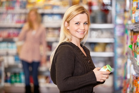 superstore: Portrait of a young woman smiling while shopping in the supermarket