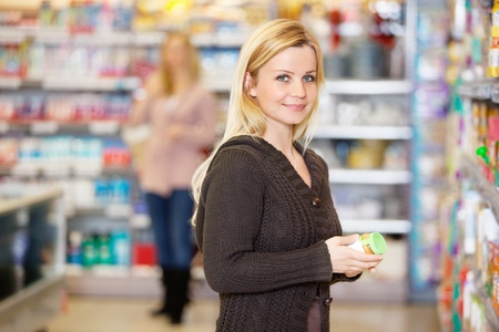 Closeup of a young woman smiling while shopping in the supermarket Stock Photo - 9470707