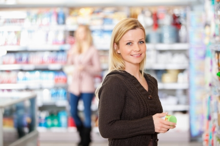 superstore: Young woman smiling while holding goods in the supermarket with people in the background