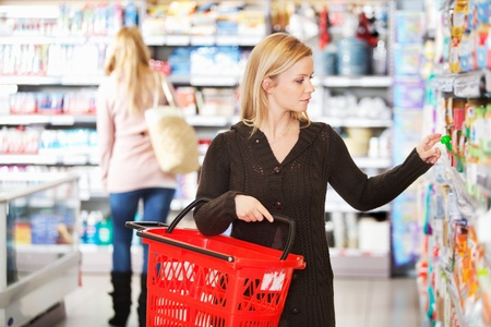 Young woman carrying basket while shopping in the supermarket photo