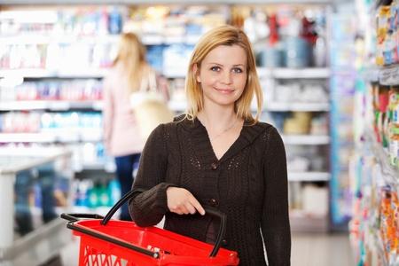 スーパー マーケットでの買い物バスケットを運ぶ若い女性の肖像画
