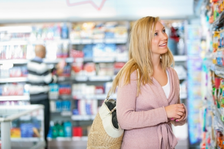 supermarket products: Young woman smiling while looking at goods in the supermarket with people in the background