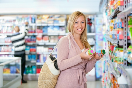Portrait of a happy young woman holding jar in the supermarket photo
