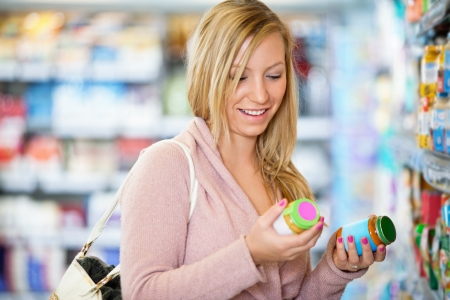 comparison: Closeup of a young woman smiling while holding jar in the supermarket Stock Photo