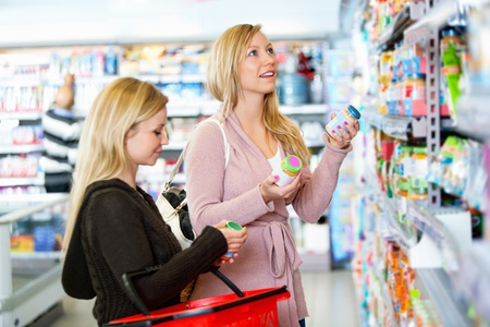 Young women shopping together in the supermarket with people in the background photo
