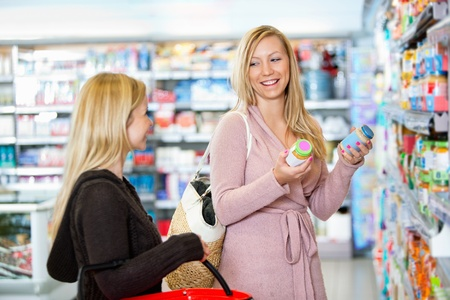 Young women shopping together in the supermarket photo