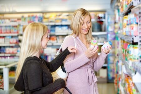 superstore: Young women smiling while shopping together in the supermarket