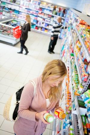 ハイアングルビュー: 食料品店で製品を比較する女性の高角度のビュー