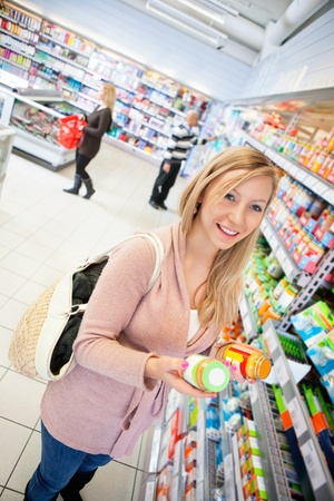 Happy young woman holding jar in the supermarket with people in the background photo