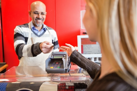 Woman passing over credit card to shop assistant after shopping Stock Photo - 9470801