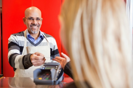 View of woman passing over credit card to shop assistant after shopping Stock Photo - 9470769