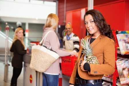 Portrait of a customer carrying pineapple in supermarket with people in the background Stock Photo - 9470679