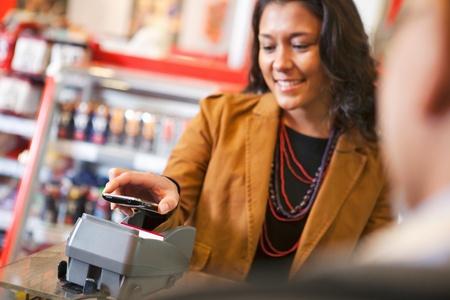 pagando: Joven pagar la compra con tel�fono m�vil Foto de archivo