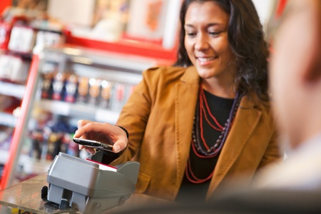 supermarket checkout: Young woman paying for purchase with cell phone Stock Photo