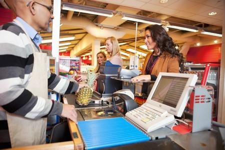 supermercado: Asistente de tienda con clientes en supermercados
