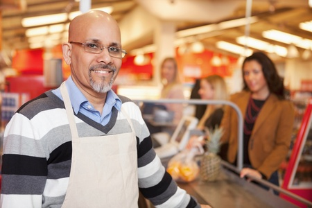 supermarket checkout: Portrait of a happy cashier with customer in the background Stock Photo