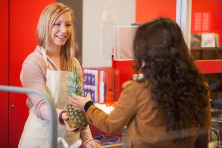 Happy shop assistant with customer in supermarket holding pineapple Stock Photo - 9470635
