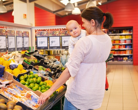 Mother carrying child while shopping in supermarket photo