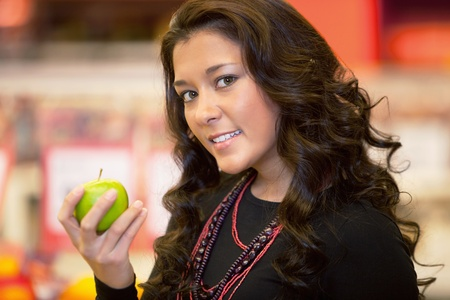 Closeup of a young woman holding apple in the supermarket Stock Photo - 9470680