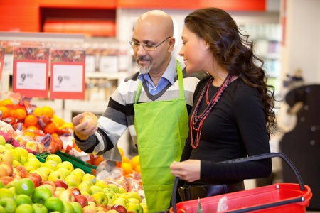 sales assistant: Shop assistant holding apple with customer in the supermarket Stock Photo