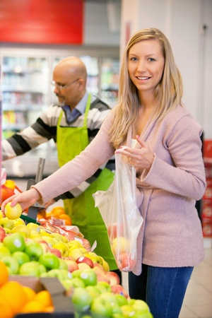 Portrait of a young woman buying fruits with shop assistant in the background photo