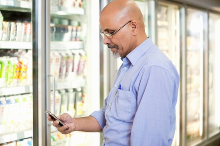 supermarket products: Smiling mature man looking at mobile phone while standing in front of refrigerator in supermarket