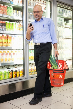 grocery basket: Man with shopping basket looking at cell phone while walking in shopping store