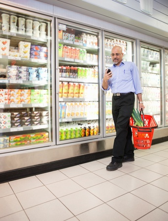 Mature man looking at mobile phone while walking in front of refrigerators in shopping centre photo