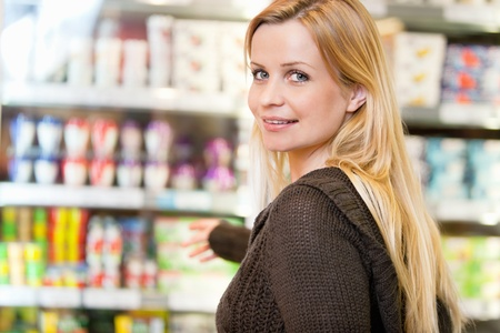 superstore: Close-up of smiling woman reaching for products arranged in refrigerator and looking at camera