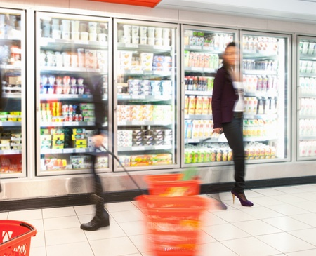 Blurred motion of people walking near refrigerator in shopping centre with baskets photo