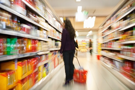shoppers: Blurred view of woman looking at products with people in the background in shopping centre Stock Photo