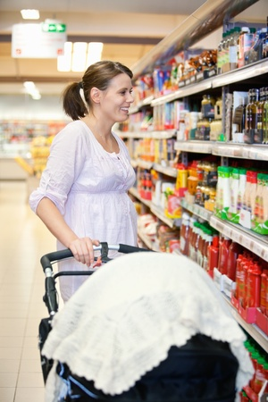 shopping carriage: Mid adult woman holding baby stroller and looking at products in shopping centre