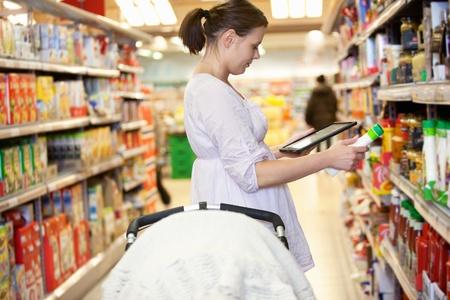 consommateurs: Femme comparant les produits avec un ordinateur tablette dans un supermarch�