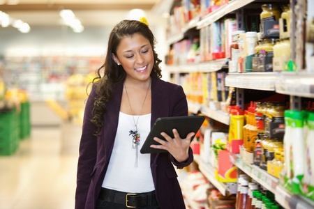 shopper: Cheerful young woman looking at digital tablet in shopping store Stock Photo
