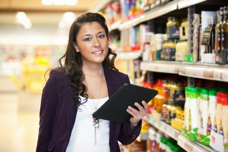 Smiling young woman looking at camera while holding digital tablet in shopping centre Stock Photo - 9470620
