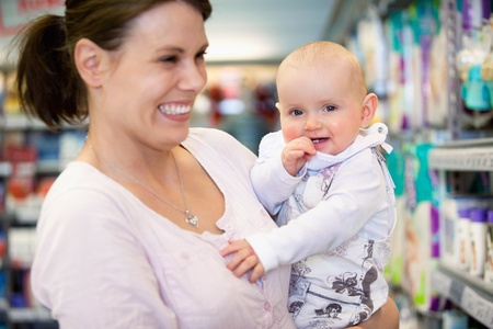 Close-up of cheerful mother and baby spending time in shopping in shopping centre, shallow depth of field of sharp focus on baby photo