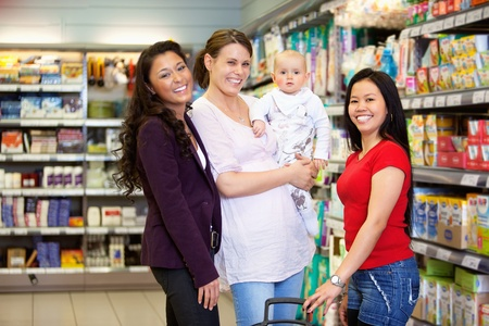 multiracial family: Woman holding baby and standing with friends while looking at camera in shopping centre