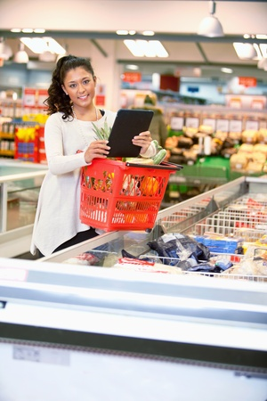 grocery trade: Shopper with basket holding shopping list on digital tablet and looking at camera