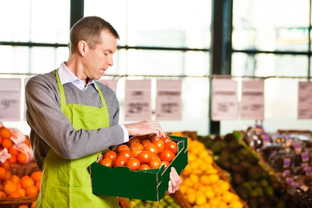 merchant: Market assistant wearing apron with holding box of tomatoes in the supermarket Stock Photo