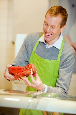 fish store: A grocery store worker with a lobster at the fish counter