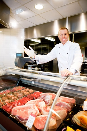 butchery: Portrait of a happy butcher welcoming customers to the shop Stock Photo